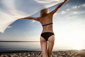 Young gorgeous blond at sunset on the beach — Stock Photo