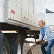 Woman Truck Driver Raising Trailer legs — Stock Photo #7744950