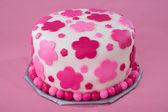 Vit sockerglasyr kaka med rosa blommor — Stockfoto