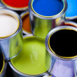 Cans and paint on the colourful background — Stockfoto