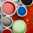 Cans and paint on the colourful background - Stock Photo
