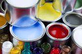 Latas e pintura sobre o fundo colorido. — Foto Stock
