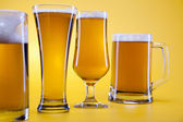 Beer glass with yellow background — Stock Photo
