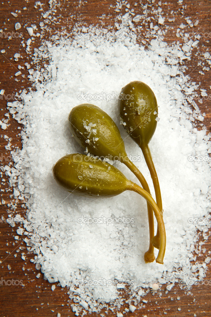 Caperberries with salt close up on wood background   Stock Photo #6870714