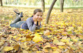 Girl lying on fall leaves outdoors — Stock Photo