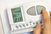 Hand pressing button on digital thermostat — Stock Photo
