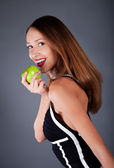 Beauty woman with apple on the grey background — Photo