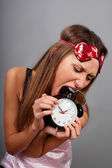 Young woman tries to eat the clock — Stock Photo