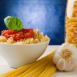 Pasta with tomato sauce on blue background — Stock Photo