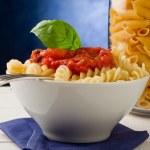 Pasta with tomato sauce on blue background — Stock Photo