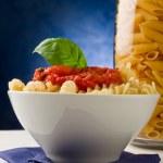macarrão com molho de tomate sobre fundo azul — Foto Stock