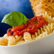 Pasta with tomato sauce and basil on blue background — Stock Photo