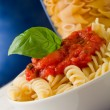 Pasta with tomato sauce and basil on blue background — Foto Stock