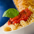 Pasta with tomato sauce and basil on blue background — Stockfoto