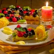 Pie with fruits and petals illuminated by candle light — Stock Photo #7309654