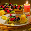 Stock Photo: Pie with fruits and petals illuminated by candle light