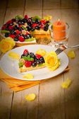 Pie with fruits and petals illuminated by candle light — Stock Photo