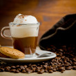 Cappuccino on coffee beans — Stock Photo