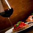 Bruschetta appetizer with red wine on wooden table — Stock Photo