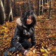 Young woman sitting on autumn forest — Stock Photo