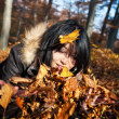Stock Photo: Womplaying with autumn leaves