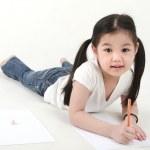 Little Asian girl drawing, lying on floo — Stock Photo #7184314