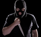 Burglar in mask holding knife — Stock Photo