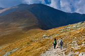Mother and son hiking into the mountains — Stock Photo