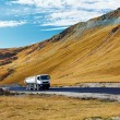 Lorry on a road through mountains - ストック写真