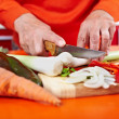 Senior woman's hands cutting vegetables - Stock Photo