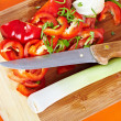 Sliced vegetables and knife on a wooden board — Stock Photo #7237731