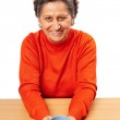 Old woman drinking from a cup — Stock Photo