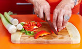 Senior woman's hands cutting vegetables — Stock Photo