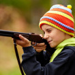 Boy playing with toy shotgun - Stock Photo
