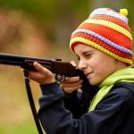 Boy playing with toy shotgun — Stock Photo #7351381