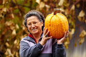 Old woman holding large pumpkin — Stok fotoğraf