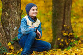 Boy in park with fallen leaves — Stock Photo