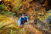 Mountaineer climbing the ladder on mountain — Stock Photo