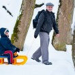 Father and son with a sledge — Stock Photo #7596050