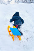 Little kid carrying a sledge uphill — Stock Photo
