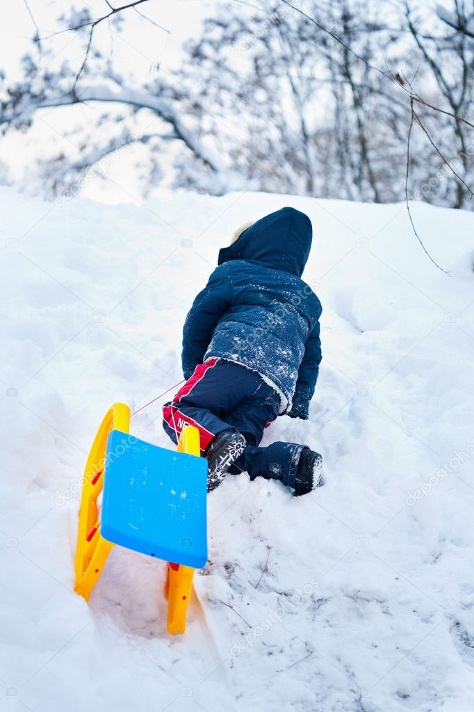 Little kid carrying a sledge uphill for another ride — Stock Photo #7596058