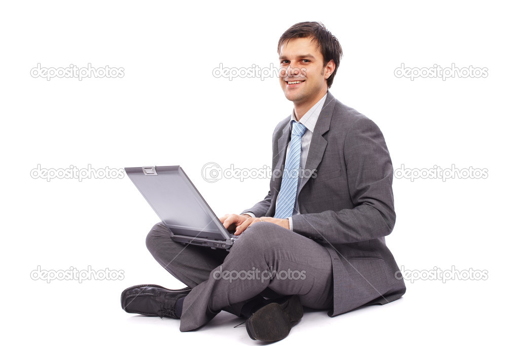 Young businessman sitting on the floor and typing on a laptop — Stock Photo #7843522