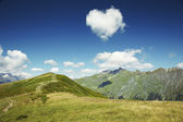 Caucasus mountains.Heart from cloud in the blue sky — Stock Photo