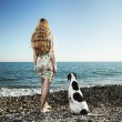 Beautiful woman with a dog on the beach — Stock Photo