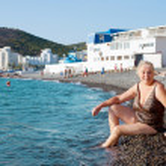 Mature woman on beach in the village of Sukko. Russia — Stock Photo