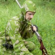 图库照片: Hunter with old rifle is considering trail