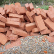 Red clay bricks lying on the gravel - Stock Photo