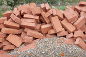 Red clay bricks lying on the gravel — Stock Photo