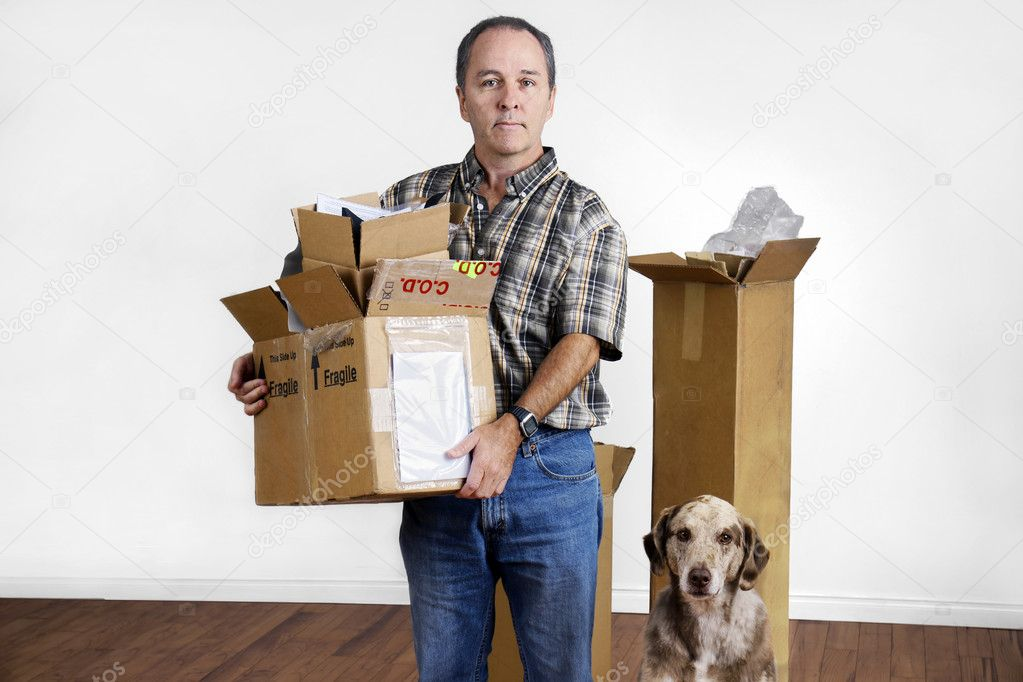 MIddle age man and dog moving out holding boxes looking sad in empty bare room. — Stock Photo #7196478