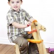 Little boy riding a rocking horse — Stock Photo